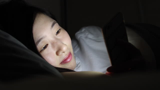 Woman using mobile phone and lying on bed video