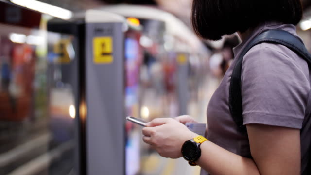 Woman using mobile phone and waiting for train , transportation