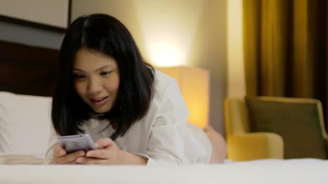 Mujer con teléfono móvil en el tiempo de descanso en el dormitorio - vídeo