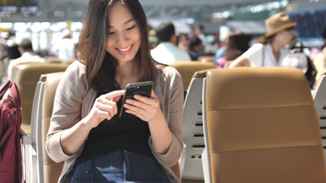 女性の空港の出発ラウンジで携帯電話を使用して ビデオ