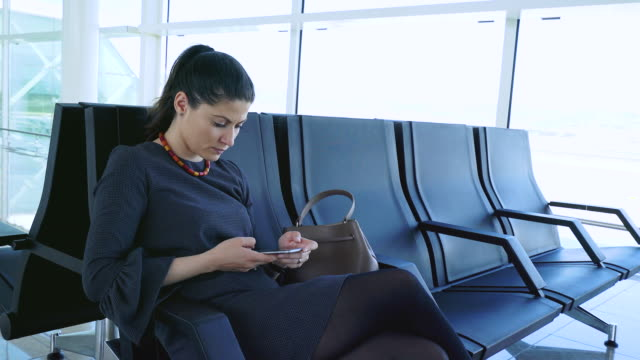Woman using mobile phone in airport. video