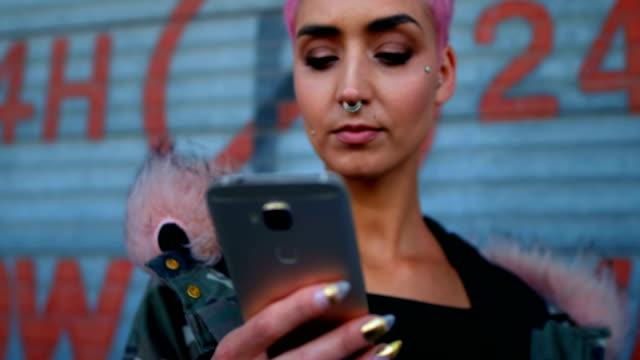 stockvideo's en b-roll-footage met vrouw met behulp van mobiele telefoon buiten winkel 4k - roze haar