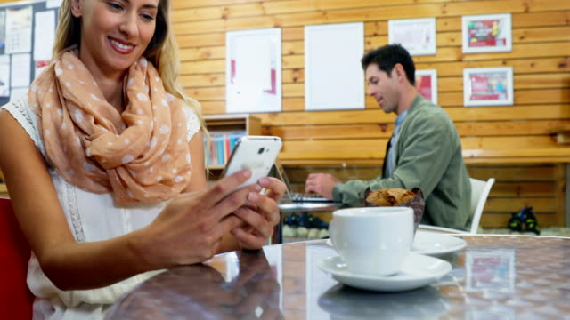 女性コーヒー 4 k をしながら携帯電話を使用して - ソーサー点の映像素材/bロール