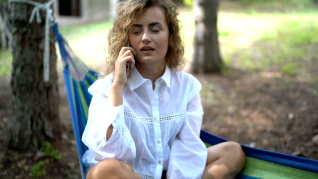 Woman using mobile phone while relaxing in a hammock video