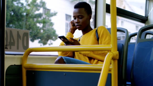 Woman using mobile phone while travelling in bus 4k video