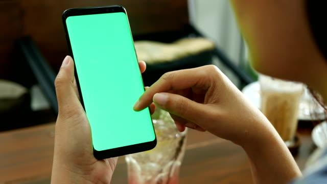 4k. kvinna använder mobil smartphone med tom grön skärm mock-up på coffee shop, använda finger beröring på skärmen och skjut, svepa, rullning gester. - skrollning bildbanksvideor och videomaterial från bakom kulisserna