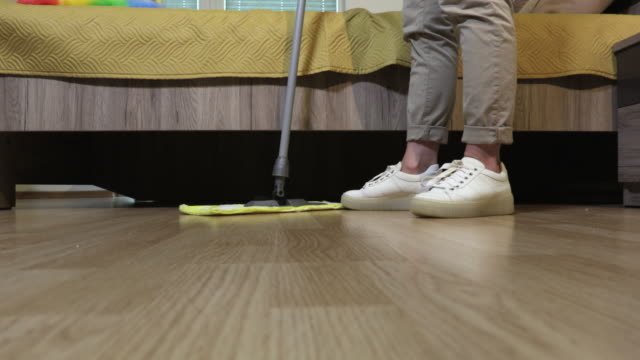 Woman using mop for floor sweeping - vídeo