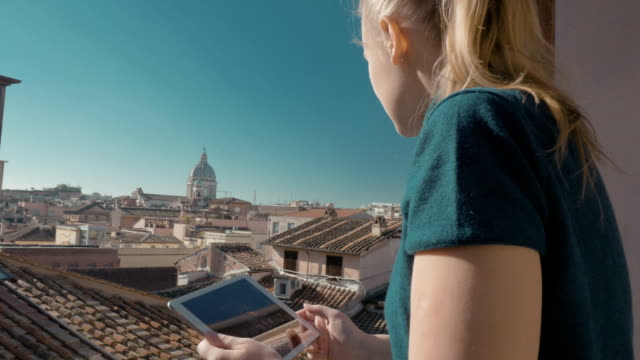 Woman using pad on the balcony with city view video