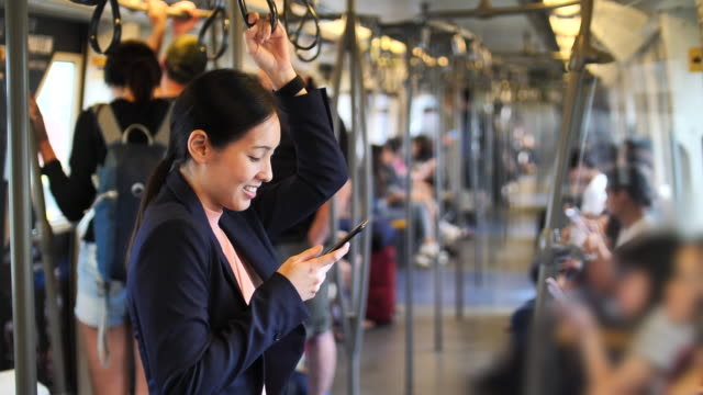 woman using phone on train - montare video stock e b–roll