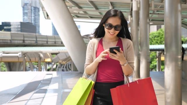 woman using phone walking with shopping bag in city, woman lifestyle - vendita al dettaglio video stock e b–roll