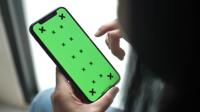 Woman using phone with green screen hold in hands