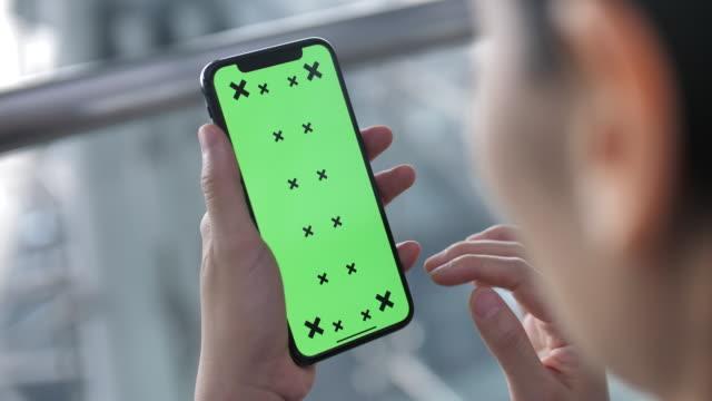 kvinna med telefon med grön skärm - skrollning bildbanksvideor och videomaterial från bakom kulisserna