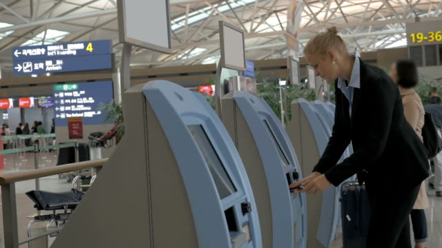 Woman using self-service machine to check-in video