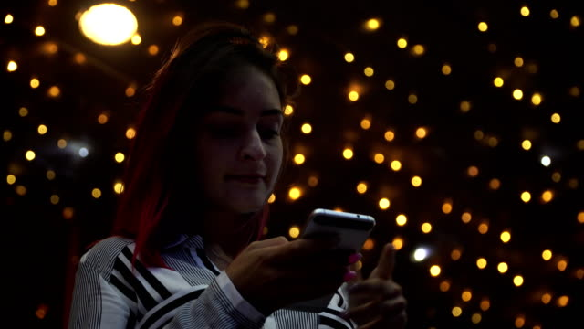 Woman using smart phone at night in city. 4K. video
