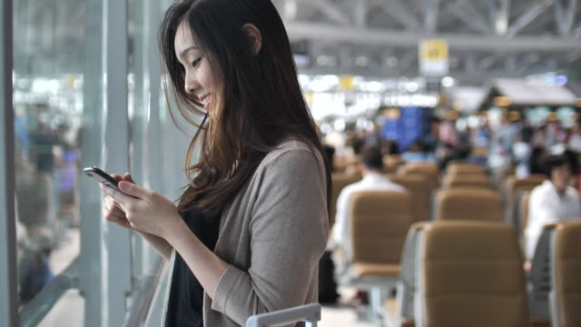 woman using smart phone at the airport - business travel stock videos and b-roll footage