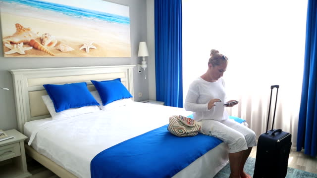 Woman using smart phone Bed hotel room video