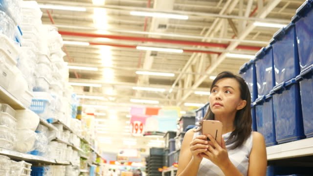Woman using smart phone in supermarket Woman using smart phone in supermarket , Close-up stationary stock videos & royalty-free footage