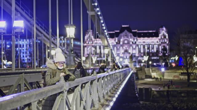 MS Woman using smart phone on urban bridge at night,Budapest,Hungary