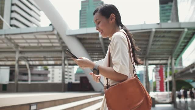 路上を歩くスマートフォンを使用する女性 - 通勤点の映像素材/bロール