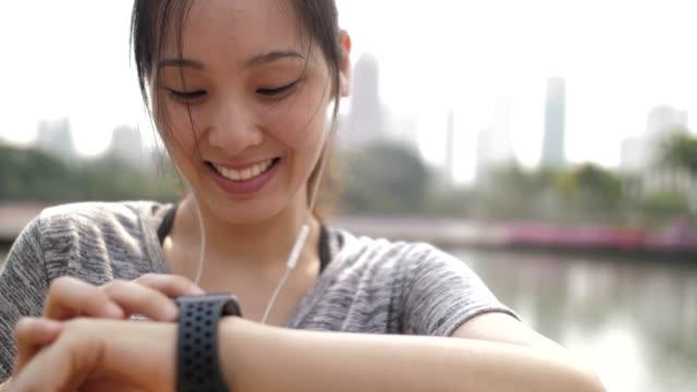 stockvideo's en b-roll-footage met vrouw met behulp van smart watch voor haar lopende prestatiecontrole op smartwatch - oost aziatische cultuur