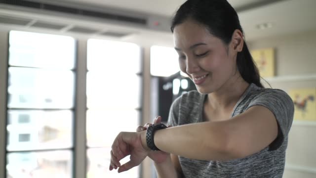 woman using smart watch while exercising for check plus - computer indossabile video stock e b–roll