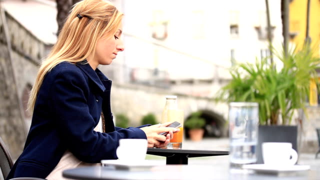 Woman using smartphone at cafe video