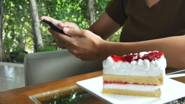 Woman using smartphone at coffee cafe with cake video
