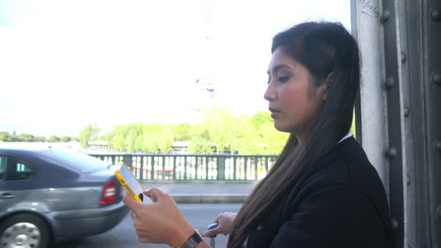 cngllei1052 woman using smartphone call a taxi on the street - paris fashion stock videos & royalty-free footage