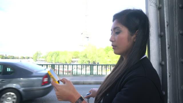 vídeos y material grabado en eventos de stock de cngllei1052 mujer usando teléfono inteligente comuníquese con el taxi en la calle - moda parisina