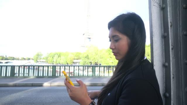 vídeos de stock, filmes e b-roll de cngllei1052 mulher usando smartphone chamar um táxi na rua - moda parisiense