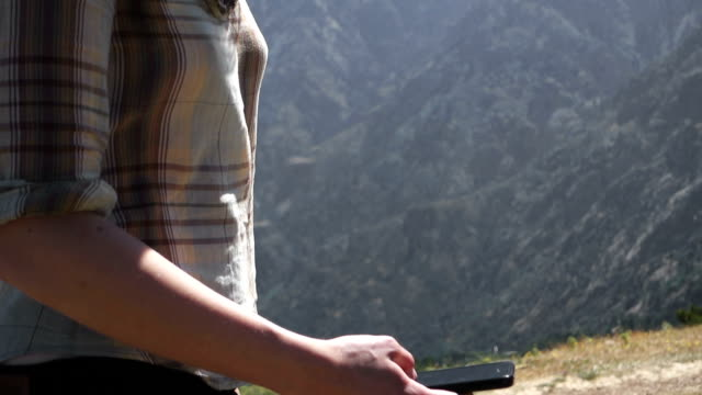 Woman using smartphone in mountain range video