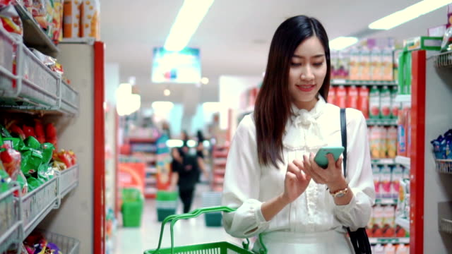 frau mit smartphone im supermarkt, slow-motion - konsum stock-videos und b-roll-filmmaterial