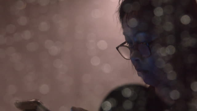 Woman using smartphone next to a window with bokeh rain drop. video