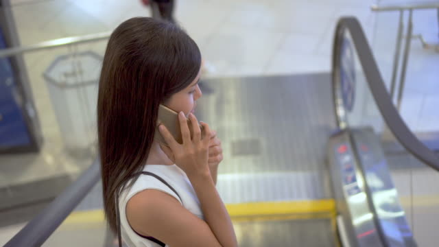 Woman using smartphone on escalator in shopping mall video