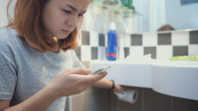 kvinna med smartphone medan du sitter på toaletten i badrummet, dolly skott - telefonmeddelande bildbanksvideor och videomaterial från bakom kulisserna