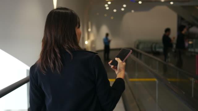 woman using smartphone while walking on corridor video