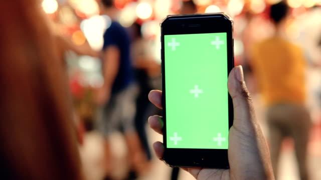 frau mit smartphone mit green-screen auf der straße - halten stock-videos und b-roll-filmmaterial