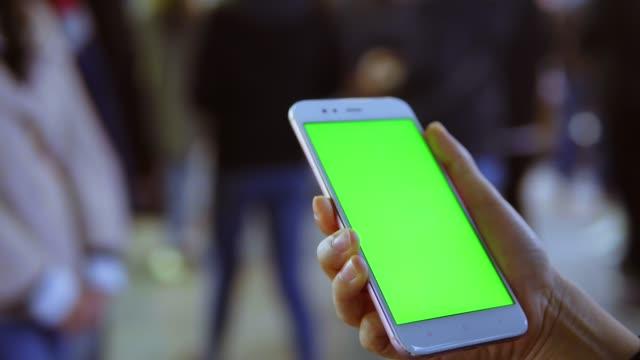 sokakta yeşil ekranlı akıllı telefon kullanan kadın - taşınabilirlik stok videoları ve detay görüntü çekimi