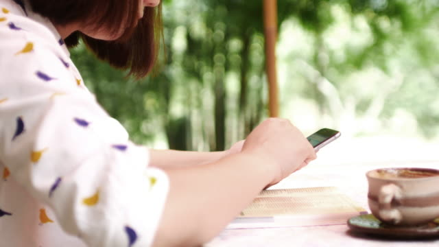 Woman using smartphone with take a coffee at coffee outdoor cafe video