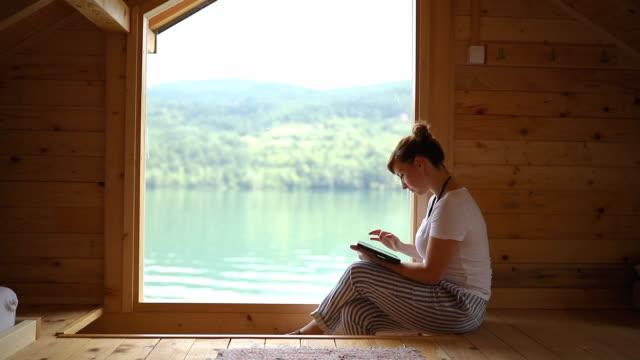 frau mit tablet und genießen in holzhaus auf see - blockhütte stock-videos und b-roll-filmmaterial