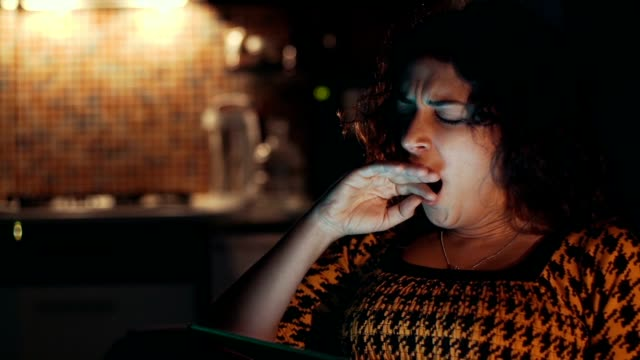 Woman using tablet computer at home Woman using tablet computer at home yawning stock videos & royalty-free footage