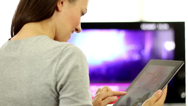Woman using tablet pc in front of tv Woman watches television while holding a tablet device cable tv stock videos & royalty-free footage