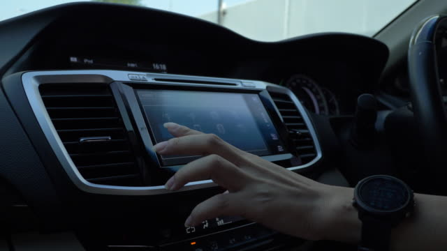woman using touch screen dashboard control in car