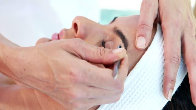 Woman using tweezers on patient eyebrow video