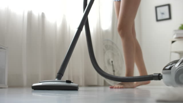 Woman using Vacuum cleaning on flooring at home