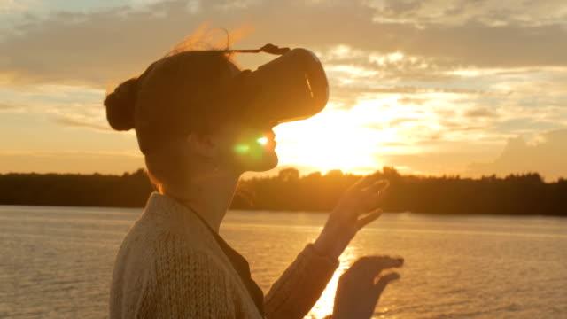 vídeos de stock, filmes e b-roll de mulher usando óculos de realidade virtual no convés do navio de cruzeiro ao pôr do sol - realidade virtual