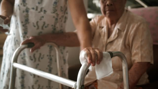 COVID-19 : Woman using wet wipe and alcohol cleaning mobility walker Coronavirus : Granddaughter using wet wipe and alcohol cleaning mobility walker, 4K Resolution granddaughter stock videos & royalty-free footage