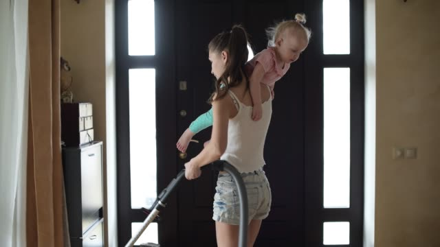 女性は彼女の腕の中に小さな娘と自宅の廊下の床を掃除機 - 家の雑用点の映像素材/bロール