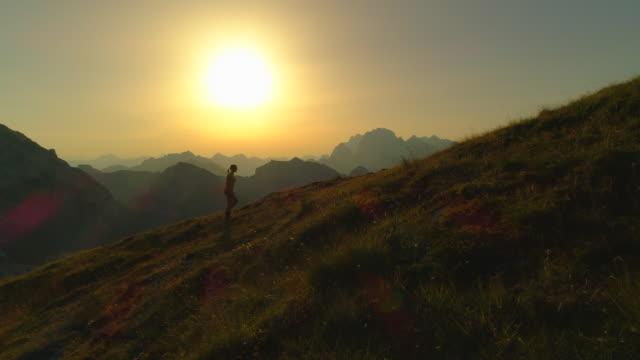 vídeos de stock e filmes b-roll de aerial silhouette woman victoriously raises arms as she reaches hilltop at dusk. - braços no ar