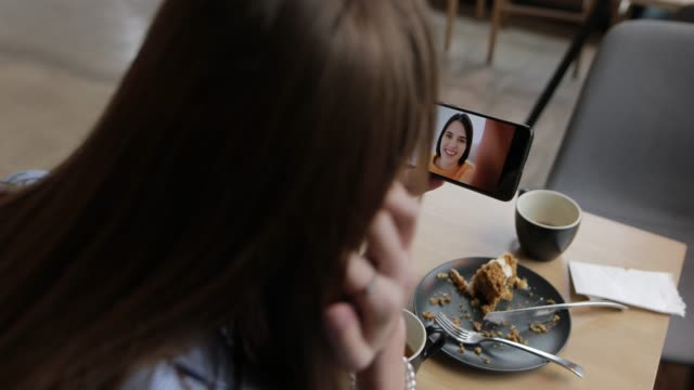 Woman video chatting with her friend holding smartphone video